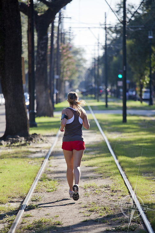 Girl running on the streetcar tracks in the Garden District of New Orleans, Louisiana.