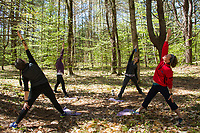 Kate Kretschmer leads Cathy Paquette, Alex Dyer and Phoebe VanScoy-Giessler into reverse warrior pose during Trail Yoga at Prescott Farm Environmental Education Center on Saturday morning.  (Karen Bobotas/for the Laconia Daily Sun)