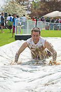 A Mud Run participant slides down the slip 'n slide filled with soap and water after completing the Race for a Reason Mud Run Saturday, April 27, 2013.  The course included a four-mile run up to the old Army ROTC Course at the Ridges, through the Radar Hill Trail and back to Tail Great Park across from Peden Stadium. Race for a Reason, Race 4 A Reason, Annual Events, Events, Students, Faculty & Staff