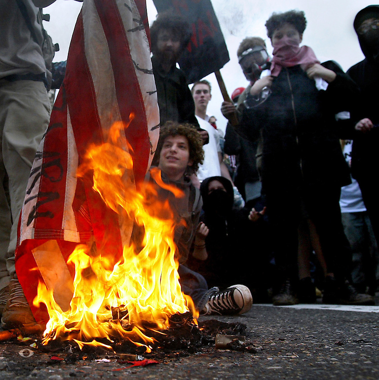 Protesters burn flags during a lengthy sit down at the intersection of SW Burnside and  2nd Avenue which lasted well into the night until Portland riot police overtook them and cleared the area.