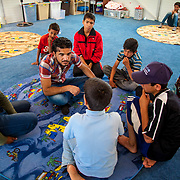 Syrian volunteer Khalid plays a game with children in a Mercy Corps adolescent friendly space. Azraq camp for Syrian refugees, Jordan, June 2014.