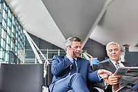 Mature businessman reading news paper while the other businessman is talking on smartphone in airport