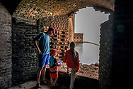 Two kids look out a window at historic Fort Jefferson with their dad on a day trip to Dry Tortugas National Park, Florida. The national park is located 70 miles west of Key West. Model released photo.