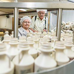 Helen LaRiviere and her husband Marc Yvan LaRiviere feed quart-sized bottles into the bottling conveyer at Maine Maple Products in Madison, Maine. The majority of the syrup bottled here is harvested in Big Six Township, Maine.