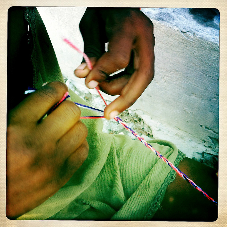 A girl makes a bracelet on Thursday, April 5, 2012 in Port-au-Prince, Haiti.