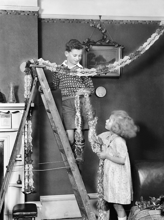 Children Hanging Christmas Decorations, England, 1932