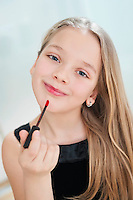 Portrait of young girl applying lipstick