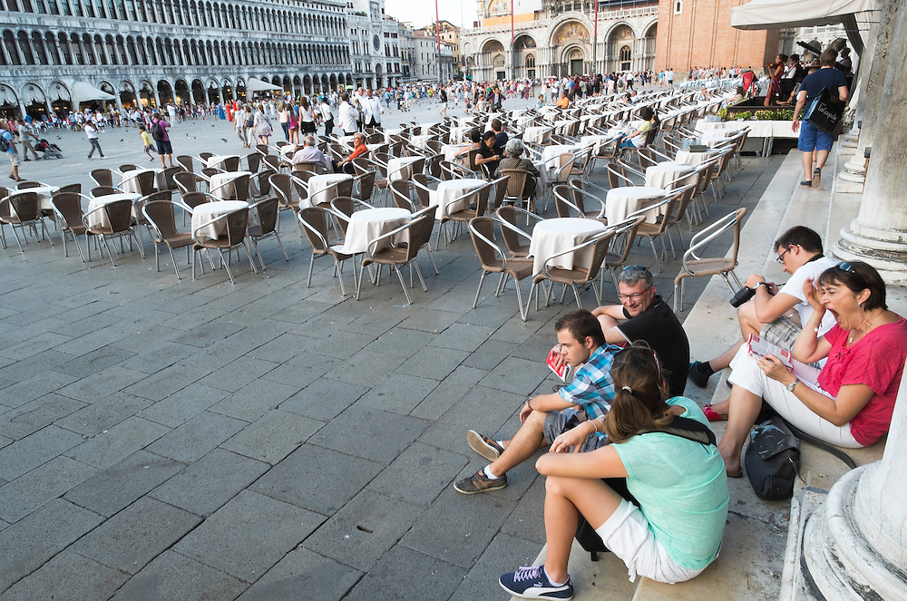 Venice August 20 Tourists sit on the steps next to the Florian Cafe.  A group of Italian tourists were horrified to be charged the equivalent of £85 for four espresso coffees laced with liqueurs in the very central Saint Mark's Square in  Venice.