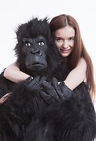 Portrait of smiling young woman hugging man in gorilla costume against white background