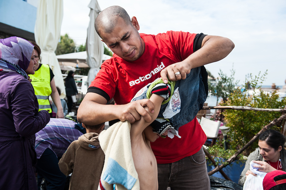 ActionAid's translator Moustafa helps Omar 10 years old from Aleppo, Syria to take off his wet clothes at the fishing harbour of Skala Sykamias, Lesvos, Greece.