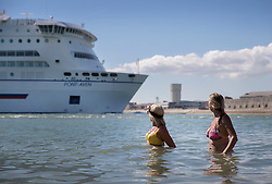 © Licensed to London News Pictures. 30/08/2016. Portsmouth, UK. Swimmers watch a Brittany Ferry from the sea in Old Portsmouth. High temperatures are being experiences in parts of the United Kingdom today. Photo credit: Peter Macdiarmid/LNP