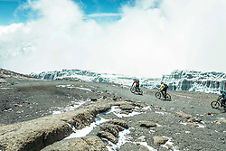 "Nov 3, 2016 - Kilimanjaro, Tanzania - Swiss-American HANS REY, German GERHARD CZERNER and Scotsman DANNY MACASKILL ride down from Kilimanjaro, passing by the remains of glaciers. Professional mountain bike riders Hans Rey, Danny MacAskill and Gerhard Czerner are the first to take on Africa's two highest mountains back to back on mountain bikes. On Oct 26th Rey and Czerner summit Africa's second tallest mountain, Mount Kenya's Point Lenana (4,985m/16,355ft) with their mountain bikes. On November 3rd, only one week later, together with urban trials YouTube sensation Danny MacAskill; they also summited Mount Kilimanjaro (5,895m/19,340ft), the Roof of Africa. There have only been a handful of people who have taken their bikes to either Mount Kilimanjaro or Mount Kenya in the past, but none have achieved both, one straight after the other. Others carried their bikes for the majority both up and down the mountains, while Rey (Swiss/American), MacAskill (Scottish) and Czerner (German) rode 98% of the descent. They are world renown extreme bikers and their feats will be featured in a TV documentary, magazine stories and an upcoming film about the Mountain Bike Freeride history, titled ""Nothin For Free"" produced by Freeride Entertainment. The hardest part about the trip was adjusting to the high altitude. The terrain is extremely technical and challenging, several different eco-systems are being crossed on the way, from rainforests to glaciers. It took the riders 4 days to summit and traverse Mount Kenya, and 6 days to summit and descend Mount Kilimanjaro. The National Parks plan on extending their programs to permit bike riders in the future. For those that dare, there are adventures and ultimate challenges both physically and mentally awaiting them. (Credit Image: © Martin Bissig via ZUMA Wire)"