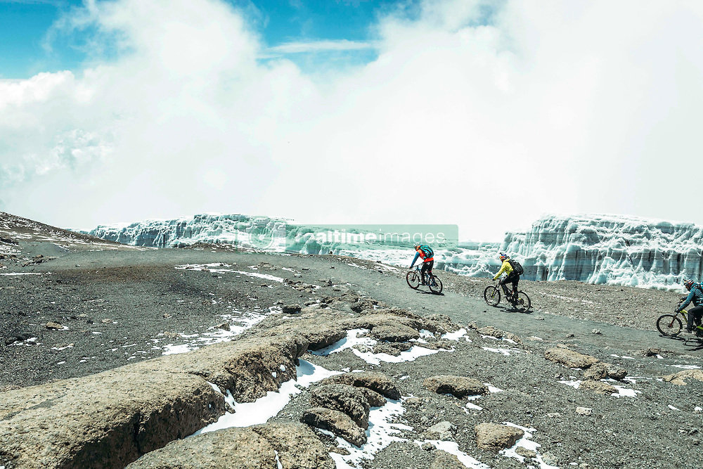 """Nov 3, 2016 - Kilimanjaro, Tanzania - Swiss-American HANS REY, German GERHARD CZERNER and Scotsman DANNY MACASKILL ride down from Kilimanjaro, passing by the remains of glaciers. Professional mountain bike riders Hans Rey, Danny MacAskill and Gerhard Czerner are the first to take on Africa's two highest mountains back to back on mountain bikes. On Oct 26th Rey and Czerner summit Africa's second tallest mountain, Mount Kenya's Point Lenana (4,985m/16,355ft) with their mountain bikes. On November 3rd, only one week later, together with urban trials YouTube sensation Danny MacAskill; they also summited Mount Kilimanjaro (5,895m/19,340ft), the Roof of Africa. There have only been a handful of people who have taken their bikes to either Mount Kilimanjaro or Mount Kenya in the past, but none have achieved both, one straight after the other. Others carried their bikes for the majority both up and down the mountains, while Rey (Swiss/American), MacAskill (Scottish) and Czerner (German) rode 98% of the descent. They are world renown extreme bikers and their feats will be featured in a TV documentary, magazine stories and an upcoming film about the Mountain Bike Freeride history, titled """"Nothin For Free"""" produced by Freeride Entertainment. The hardest part about the trip was adjusting to the high altitude. The terrain is extremely technical and challenging, several different eco-systems are being crossed on the way, from rainforests to glaciers. It took the riders 4 days to summit and traverse Mount Kenya, and 6 days to summit and descend Mount Kilimanjaro. The National Parks plan on extending their programs to permit bike riders in the future. For those that dare, there are adventures and ultimate challenges both physically and mentally awaiting them. (Credit Image: © Martin Bissig via ZUMA Wire)"""