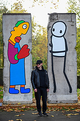 © Licensed to London News Pictures. 05/11/2019. LONDON, UK.  Street artist STIK poses as the unveiling of new work by artists Theirry Noir (L) and STIK (R) on original Berlin Wall sections to mark 30 years since the fall of the Berlin Wall.  Located outside the Imperial War Museum, the new works reflect the symbolic connections between the Berlin Wall and street art and the fall of the wall on 9 November 1989.  These new works are on display until 1 December.  Photo credit: Stephen Chung/LNP