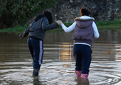 ©London News pictures... 17/11/2010. Two girls make their way through the water.A couple abandon their car is rising flood water. The River Fowey burst its banks at Lost Withiel in Cornwall. today (Wednesday). Some people have been left trapped in their cars and homes in parts of Cornwall as heavy rain and gale-force winds caused flooding and disruption.