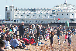© Licensed to London News Pictures. 25/03/2016. Brighton, UK.  Thousands of people relax in the sun on Brighton Beach at the start of the Easter Bank Holliday weekend. Photo credit: Hugo Michiels/LNP