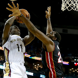 Oct 23, 2013; New Orleans, LA, USA; New Orleans Pelicans point guard Jrue Holiday (11) shoots over Miami Heat center Greg Oden (20) during the first half of a preseason game at New Orleans Arena. Mandatory Credit: Derick E. Hingle-USA TODAY Sports