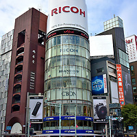 Introduction to the Ginza in Tokyo, Japan <br /> If you are serious about shopping, then you must visit Ginza. It is always listed among the top ten retail districts in the world. Squeezed into eight blocks are every major luxury brand plus plenty of department stores and boutiques. You will also find an array of restaurants &ndash; ranging from cheap to extravagant &ndash; plus night clubs for social insomniacs. The main street is Chuo-dori and the heart is this Ginza 4-chome Intersection. Just watch for the flashing neon sign atop the famous glass cylinder of the San-ai Building. The word &ldquo;Ginza&rdquo; means &ldquo;seat of silver.&rdquo; Its origin is when a coin mint was built here in 1612 during the Edo period (1603 &ndash; 1868).