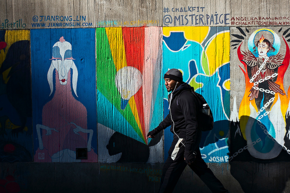 Man walking past chalk art on concrete wall, New York, NY, US