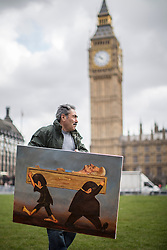 © licensed to London News Pictures. London, UK 15/04/2013. Kaya Mar posing in Parliament Square, London with his new painting which criticises Margaret Thatcher's death and funeral. Photo credit: Tolga Akmen/LNP