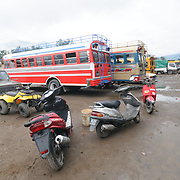 Chicken buses and scooters behind the Mercado Municipal (town market) in Antigua, Guatemala. From this extensive central bus interchange the routes radiate out across Guatemala. Often brightly painted, the chicken buses are retrofitted American school buses and provide a cheap mode of transport throughout the country.