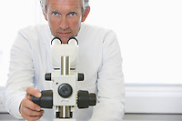 Scientist working behind microscope in laboratory
