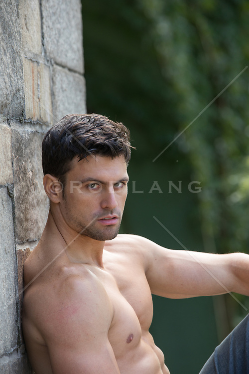 portrait of a shirtless man outdoors