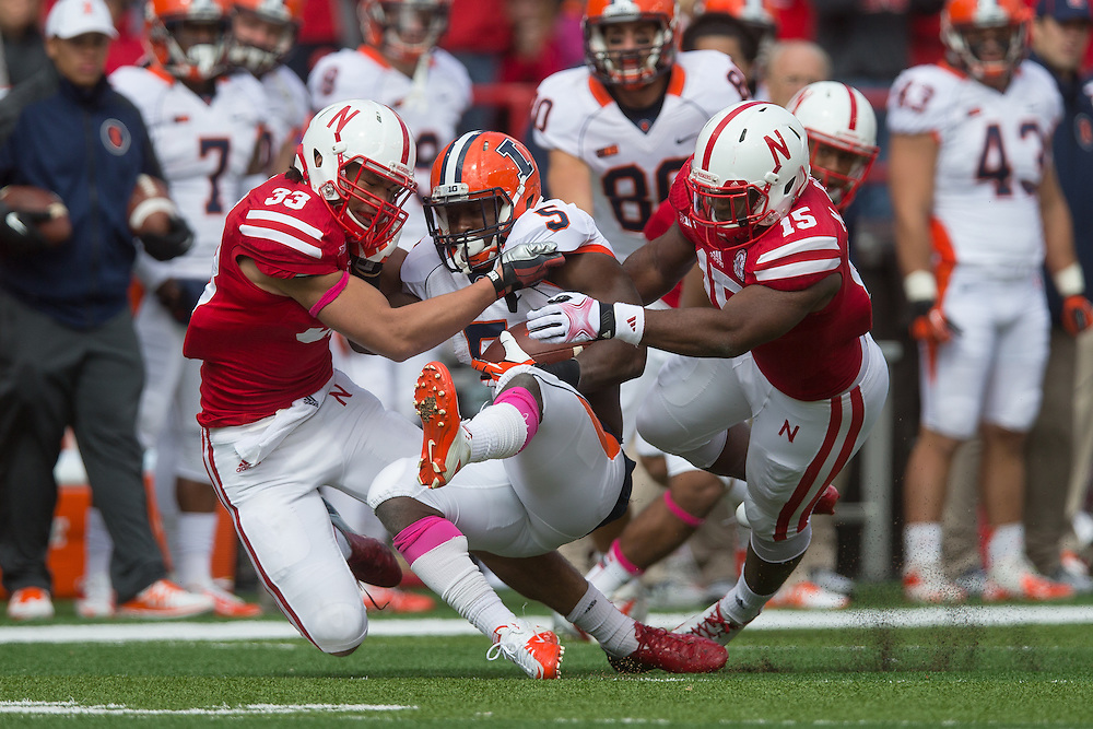 Linebacker Jared Afalava (33) and linebacker Michael Rose (15) of the Nebraska Cornhuskers tackle Illinois running back Donovonn Young (5) during a 39-19 Husker victory. Photo by Scott Bruhn