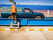 "15 DECEMBER 2014 - CHUM SAENG, RAYONG, THAILAND: A farmer stands in front of his pickup truck while his load of latex is weighed at a rubber buying station in Chum Saeng, Thailand. Thailand is the second leading rubber exporter in the world. In the last two years, the price paid to rubber farmers has plunged from approximately 190 Baht per kilo (about $6.10 US) to 45 Baht per kilo (about $1.20 US). It costs about 65 Baht per kilo to produce rubber ($2.05 US). Prices have plunged 5 percent since September, when rubber was about 52Baht per kilo. Some rubber farmers have taken jobs in the construction trade or in Bangkok to provide for their families during the slump. The Thai government recently announced a ""Rubber Fund"" to assist small farm owners but said prices won't rebound until production is cut and world demand for rubber picks up.    PHOTO BY JACK KURTZ"