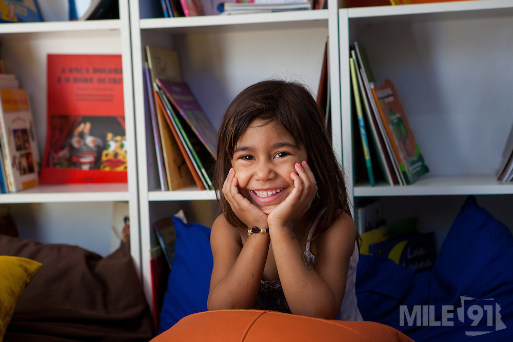 Diully Stefane Zanoni smiling at the camera in the community library, Biblioteca Comunitaria do Arquipelago, Porte Alegre, Brazil. <br /> <br /> Cirandar is working in partnership with  C&A and C&A Instituto to implement a network of Community Libraries in eight communities of Porto Alegre.
