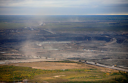 CANADA ALBERTA FORT MCMURRAY 28SEP09 - Aerial view of the Suncor tarsands mining operation in the Boreal forest north of Fort McMurray, northern Alberta, Canada...The tar sand deposits lie under 141,000 square kilometres of sparsely populated boreal forest and muskeg and contain about 1.7 trillion barrels of bitumen in-place, comparable in magnitude to the world's total proven reserves of conventional petroleum. ..Current projections state that production will  grow from 1.2 million barrels per day (190,000 m³/d) in 2008 to 3.3 million barrels per day (520,000 m³/d) in 2020 which would place Canada among the four or five largest oil-producing countries in the world...The industry has brought wealth and an economic boom to the region but also created an environmental disaster downstream from the Athabasca river, polluting the lakes where water and fish are contaminated. The native Indian tribes of the Mikisew, Cree, Dene and other smaller First Nations are seeing their natural habitat destroyed and are largely powerless to stop or slow down the rapid expansion of the oil sands development, Canada's number one economic driver...jre/Photo by Jiri Rezac / GREENPEACE..© Jiri Rezac 2009