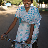 "Vasanti on a bike on which she commutes to and from her work at the Save Foundation in Sangli city...Like many of the women who work for and with UNDP partners the Save Foundation, Vasanti Shinde, age 26, only found out that she was HIV positive after her husband became seriously ill with an AIDS-related illness five years ago. Vasanti's husband subsequently died. Vasanti now lives with her two younger daughters Shrudha, age 10, and Vrinda, 8, in the one-room home of her brother in Sangli city. Vasanti's elder daughter, eleven year old Shubhada is being brought up by her paternal grandmother and sees her mother during holidays. Vasanti knows that Shubhada is HIV negative and Shruda is positive but anxiety over the result means that she refuses to have Vrinda tested for HIV. For a monthly income of Rs.3500, Vasanti works as a field officer and counselor for the Save Foundation. She works in the positive-people's pharmacy for no pay. Her work with the Save Foundation entitles her access to a credit union which provides low interest loans covering medical expenses. Though first-line drugs and homeopathic medicine keep Vasanti healthy, she is prone to infection and recently suffered a bout of influenza. Vasanti is completely open about her HIV status and most of her neighbours know that she is HIV positive. Vasanti says that ""I used to feel like I was going to die. Now, because of the Save Foundation, I feel like I'm going to live."" ..Photo: Tom Pietrasik.Sangli, Maharashtra. India.August 27th 2008..THIS PHOTOGRAPH IS THE COPYRIGHT OF TOM PIETRASIK. THE PHOTOGRAPH MAY NOT BE REPRODUCED IN ANY FORM OTHER THAN THAT FOR WHICH PERMISSION WAS GRANTED. THE PHOTOGRAPH MAY NOT BE STORED OR MANIPULATED WITHOUT PRIOR PERMISSION FROM TOM PIETRASIK...Tom Pietrasik.PHOTOGRAPHER.NEW DELHI.India tel: +91 9810614419.UK tel: +44 7710507916.Email: tom@tompietrasik.com.Website: tompietrasik.com"