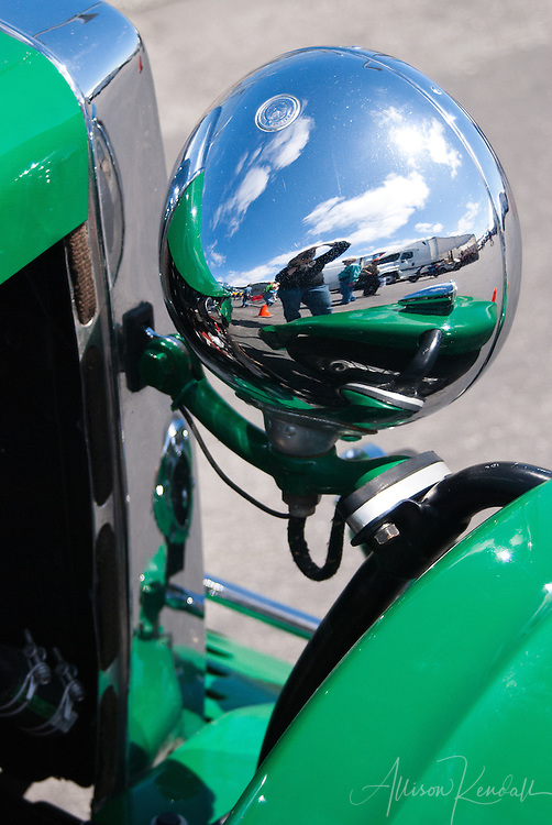 Self-portrait, reflected in vintage auto headlight at Laguna Seca during the Reunion events of Monterey Car Week
