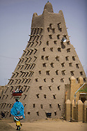 Woman passing in front of Sankoré Mosque, in Timbuktu, Mali.