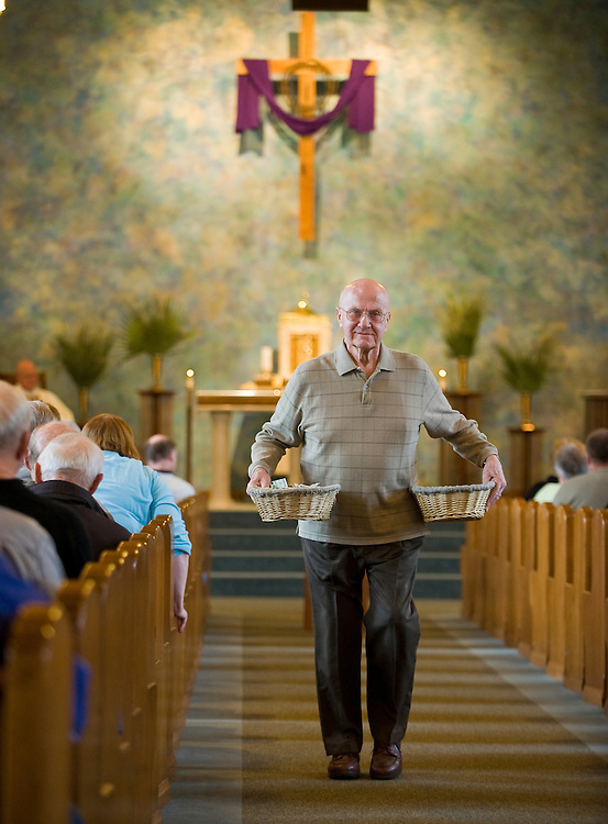 An usher carries collection baskets at St. Philip Church in Green Bay. (Sam Lucero photo)
