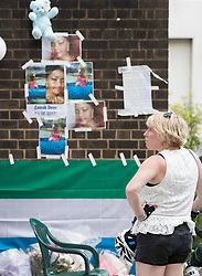 © Licensed to London News Pictures. 18/06/2017. London, UK. A woman looks at posters of the missing near site of the burnt out Grenfell tower block . The blaze engulfed the 27-storey building killing dozens - with 34 people still in hospital, many of whom are in critical condition. The fire brigade say that they don't expect to find anyone else alive. Photo credit: Peter Macdiarmid/LNP
