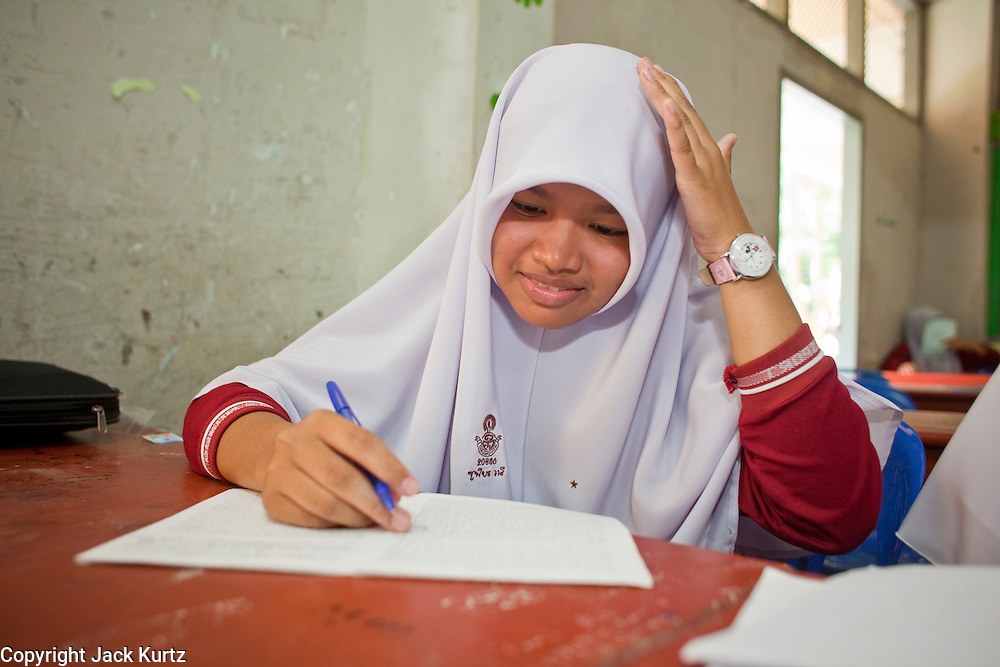 """Sept. 29, 2009 -- SAI BURI, THAILAND: A girl in an Islamic studies class at the Darunsat Wittya Islamic School in Sai Buri, Thailand. The school is the largest Muslim high school in Pattani province. Although it is a private school, the Thai government pays students' tuition to attend the school. The curriculum combines Thai official curriculum with Islamic curriculum. Many of the students go on to college level education in Egypt and Saudi Arabia. The Thai government views Islamic high schools with suspicion, fearing they radicalize students. Thailand's three southern most provinces; Yala, Pattani and Narathiwat are often called """"restive"""" and a decades long Muslim insurgency has gained traction recently. Nearly 4,000 people have been killed since 2004. The three southern provinces are under emergency control and there are more than 60,000 Thai military, police and paramilitary militia forces trying to keep the peace battling insurgents who favor car bombs and assassination.   Photo by Jack Kurtz / ZUMA Press"""