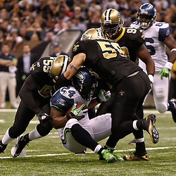 November 21, 2010; New Orleans, LA, USA; New Orleans Saints defenders linebacker Danny Clark (55), linebacker Scott Shanle (58) and defensive lineman Jimmy Wilkerson (99) combine to tackle Seattle Seahawks running back Marshawn Lynch (24) during the second half at the Louisiana Superdome. The Saints defeated the Seahawks 34-19. Mandatory Credit: Derick E. Hingle