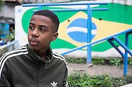 A young Brazilian in front of a Brazilian flag mural in the Santo Amaro favela, Rio de Janeiro, Brazil. According to Patrick Ashcroft an English (Stockport) researcher and teacher who lives in the favela, it is fairly quiet and non violent. There is a heavily armed police presence in the favela.<br /> Picture by Andrew Tobin/Focus Images Ltd +44 7710 761829<br /> 20/06/2014