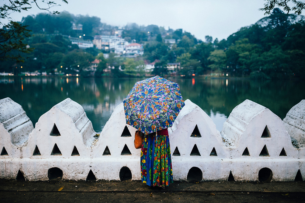 Kandy, Sri Lanka -- January 31, 2018: A woman in colorful dress looks out over Bogambara Lake.