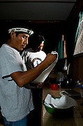 Mayan Lab workers get up in the middle of the night to feed Scarlet Macaws that are being monitored for eventual release.