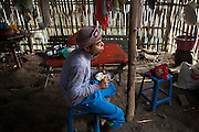 Ko Aung Myo having breakfast after the hard work in the palm tree tops. At Ka Myaw Gyi village in the outskirts of Dawei, Myanmar.