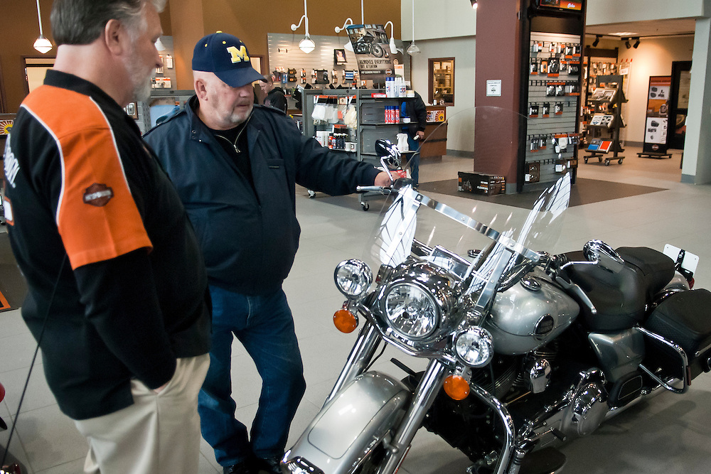 Lathan Goumas | MLive.com..March 29, 2012 - Tom Edwards of Genese Township talks to  salesman Jim Williamson while looking at motorcycles at Vehicle City Harley-Davidson in Flint Township on Thursday. Michigan Governor Rick Snyder has been sent a bill by the state's legislature that if signed would repeal the motorcycle helmet requirement law.
