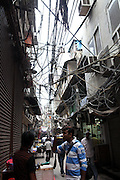 """Packed lanes, dangling power lines make Old Delhi firetrap<br /> <br /> It doesn't take a rocket scientist to figure out the dangers that old Delhi's crammed alleyways with dangling power lines pose to anyone living<br /> <br /> This is the famous area Chandini Chowk in Old delhi and the electricity lines provide connections to houses and shops in that area.<br /> <br />  The danger is worse during the monsoon season. According to fire department officials, the tangle of naked wiring over Walled City is a major cause for concern. """"It takes just one spark for the entire market to go up in flames,"""" said a fire official.<br /> <br /> Rampant commercialization and consequent unauthorized construction has only added to the problem. Congestion has increased further and there is often little or no space between buildings. Sadar Bazaar is generally packed to capacity with shoppers, with auto drivers, cycle-rickshaws and cars jostling for space in the lanes. Old, precariously-placed, open transformers lie in their midst like deathtraps. If there is a fire, there is no escape route. Shockingly enough, several shops here lack fire safety measures.  <br /> ©Exclusivepix Media"""