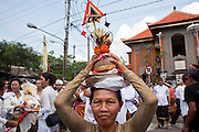 Apr. 25 -- UBUD, BALI, INDONESIA:   A mourner in the procession at the funeral for Cokorde Gede Raka, a member of Ubud's royal family Sunday, Apr. 25. Balinese are Hindus and cremate their dead. Balinese funerals are elaborate - and expensive - affairs. A funeral for one person costs a minimum of 45 million rupiah (about $5,000 US). The body is placed into the bull's body at the cremation and cremated in the bull. The funeral pyre is burnt adjacent to the bull. That is what a family may earn in two to three years. The result is that only the rich can afford formal cremations. The body (in the casket) is placed in the top of the funeral pyre and the procession takes the body to the cremation site. The funeral pyre, and the body, are spun at intersections to confuse the spirits so the soul doesn't try to return to its home and to confuse evil spirits.    PHOTO BY JACK KURTZ