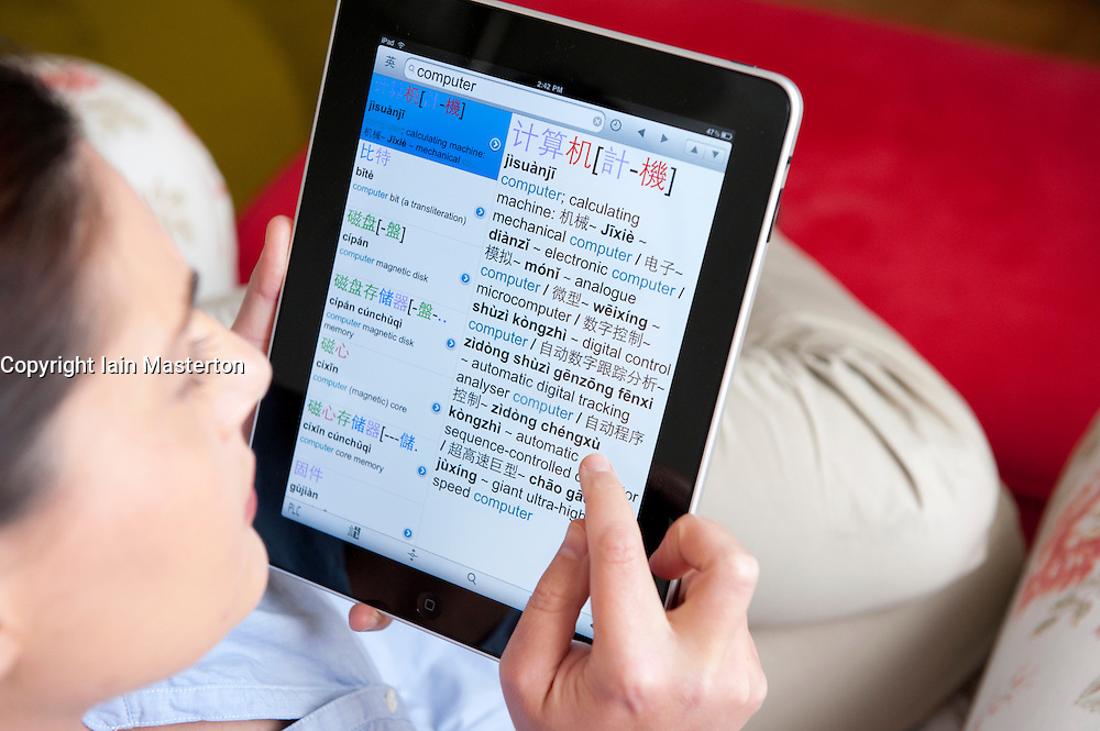 Woman studying Chinese language using iPad tablet computer to check spelling of Chinese words in dictionary