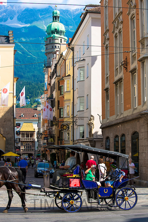 Tourists view Goldenes Dachl, Golden Roof, from horse-drawn carriage by Herzog Friedrich Strasse, Innsbruck the Tyrol Austria