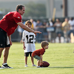 August 6, 2011; Metairie, LA, USA; New Orleans Saints quarterback Drew Brees (9) plays with his son Baylen Brees and other children following training camp practice at the New Orleans Saints practice facility. Mandatory Credit: Derick E. Hingle