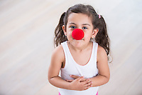 Portrait of cute little girl wearing clown nose at home