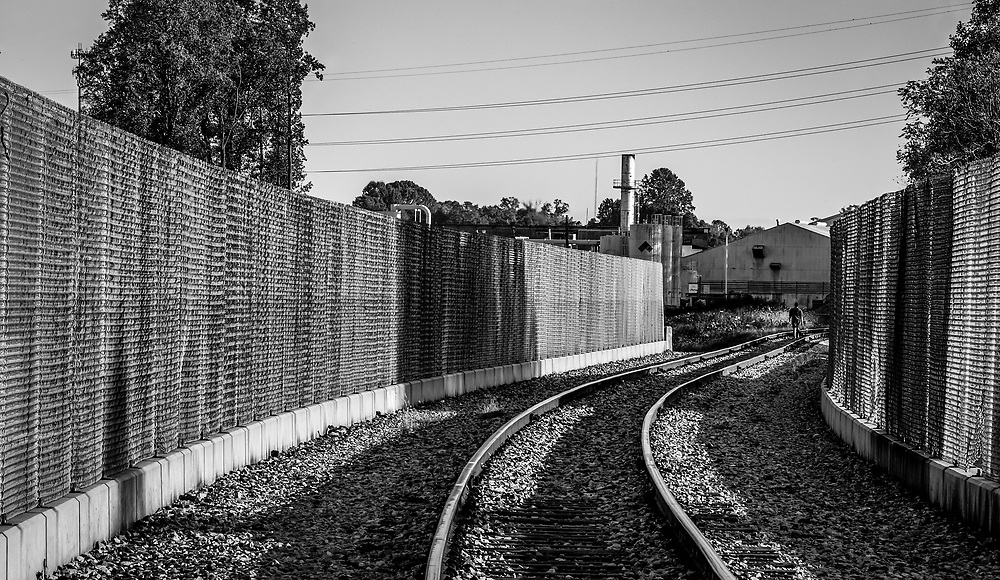 The lines in the composition lead to an indivdual making his way home southbound on this railroad track in WInston-Salem, NC.